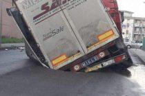 Voragine nel manto stradale, sprofonda un camion